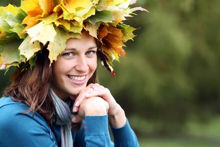 Beautiful woman with diadem made from yellow maple leaves   photo