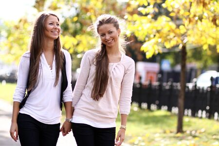 Two cheerful girls twins, in the street photo
