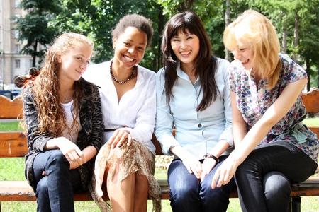 adolescentes riendo: cuatro mujeres hablando juntos en la calle