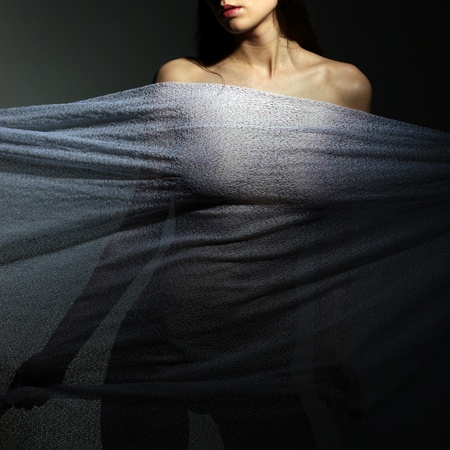 Anonymous nude of girl silhouetted behind sheer cloth