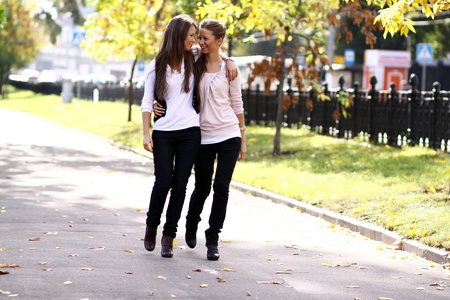 identical: Fashionable girls twins walk in the street Stock Photo