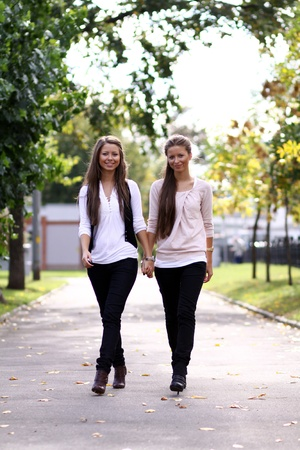 Fashionable girls twins walk in the street Stock Photo - 8639531