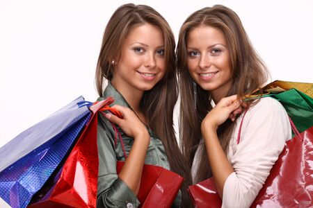 Twins sisters holding shopping bags on white isolated   photo