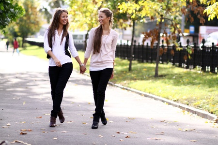 18's: Fashionable girls twins walk in the street Stock Photo