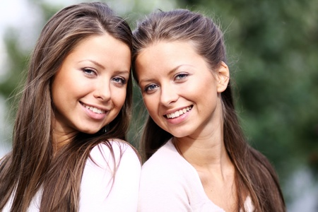 Twins of sister - women in summer park photo