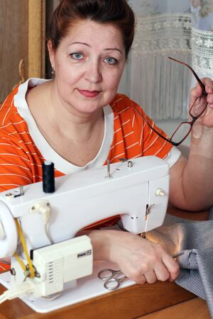old woman sews clothes in-home  photo