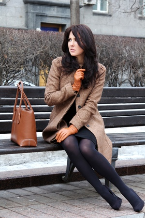 The beautiful young city woman sits on a bench photo
