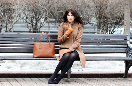 sits: The beautiful young city woman sits on a bench