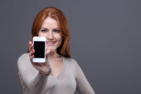 Portrait of a confident young woman showing mobile phone against grey background Stock Photo - 11361016