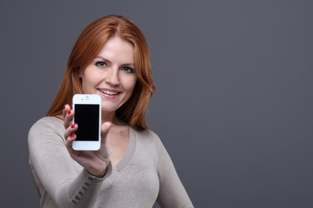Portrait of a confident young woman showing mobile phone against grey background