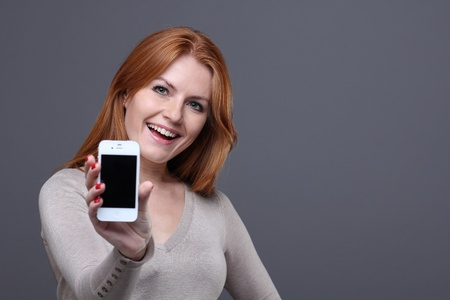 Portrait of a confident young woman showing mobile phone against grey background  photo