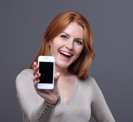 woman phone: Portrait of a confident young woman showing mobile phone against grey background