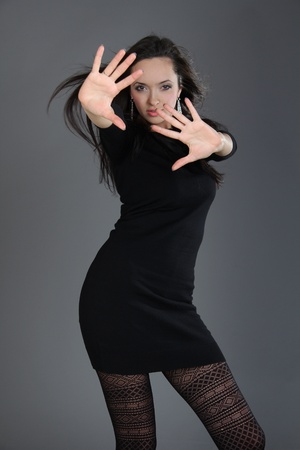 young woman in black dress. Isolated over dark background. photo