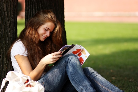 portrait of young beautiful woman reading magazine  Stock Photo