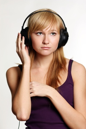 Isolated smiling young girl listening to music  photo