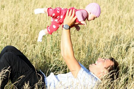 father and baby play on outdoor photo