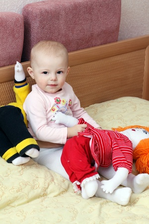 1 2 month: baby sitting on a bed with two dolls� Stock Photo