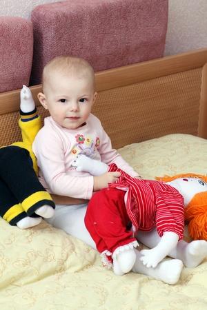 meses del a�o: beb� que se sienta en una cama con dos dolls� ��
