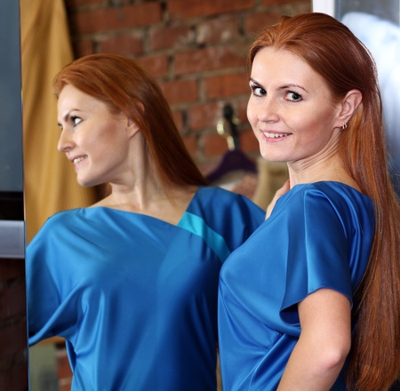 red head woman: beautiful red-haired woman posing in front of a mirror