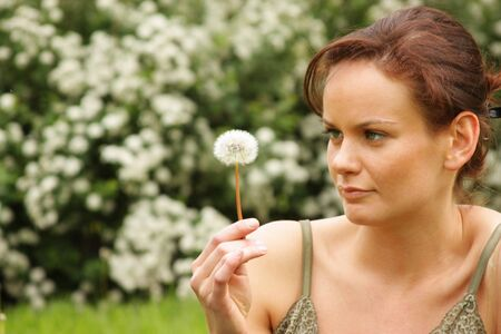 young woman blowing on the dandelion  photo