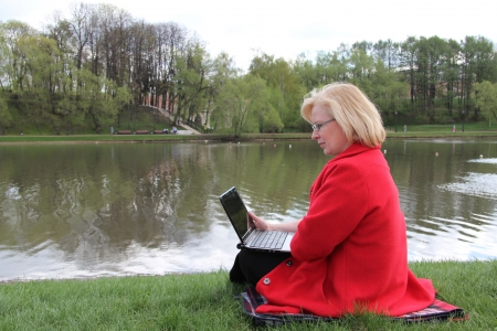 an elderly woman sitting with a laptop in a spring park photo