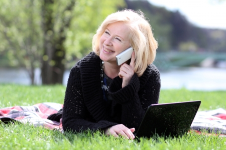 portrait of a happy mature woman calling by phone photo