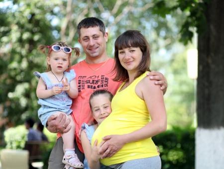 homme enceinte: Famille de quatre � l'ext�rieur jouissant