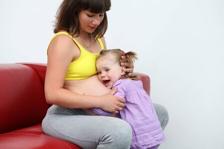 portrait of excited young girl listening to her pregnant mother belly  photo