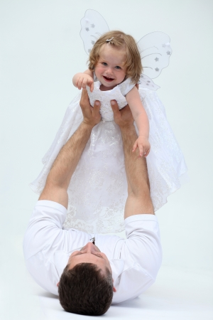 Father holding his hands on the little girl photo
