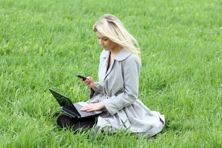 young girl sitting on grass with laptop and phone photo