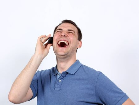 madman: Smiling young man on his mobile phone against a white background Stock Photo