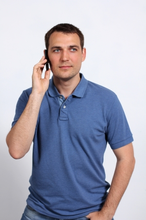 young man on his mobile phone against a white background photo