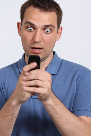 oung guy sending a sms with his mobile phone photo