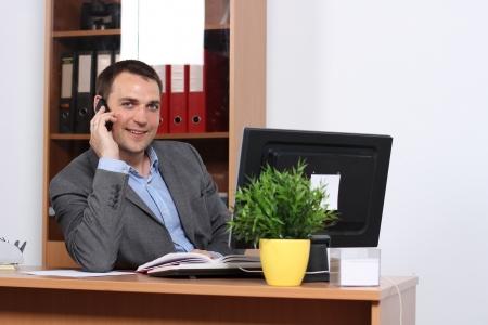 Smiling man talking on mobile phone photo