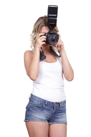 Cheerful woman shooting with a camera against white background  photo
