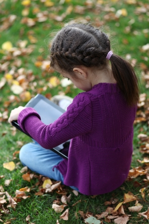 Little Girl holding tablet digital computer photo
