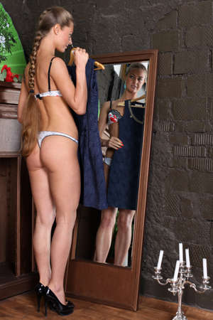 girl tries on an evening dress in the mirror