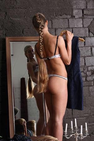 ass standing: girl tries on an evening dress in the mirror