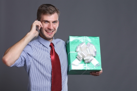 celphone: Portrait of young business man with gifts Stock Photo