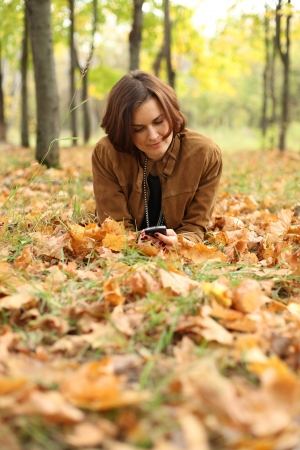 woman lying on a carpet of leaves in autumn park  photo