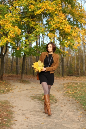 Full length, walking woman in autumn park photo