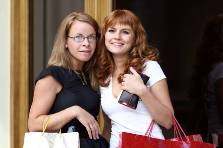 two happy women with shopping in a store photo