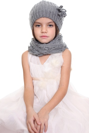little girl in a knitted hat and gray scarf photo