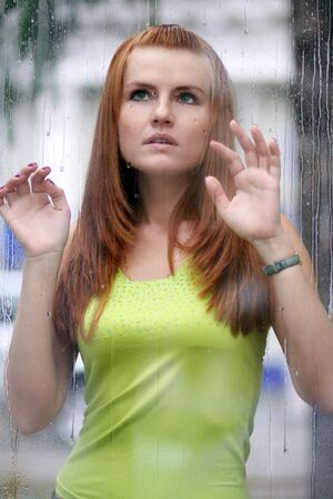 Portrait of a lovely young lady looking through glass window Stock Photo - 16603267