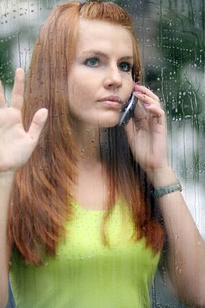 Portrait of a lovely young lady looking through glass window photo