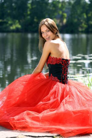 sensuous: Smiling woman in a red dress sitting near river