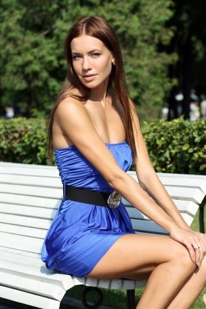 mujeres sentadas: Hermosa mujer joven sentada en un banco del parque Foto de archivo