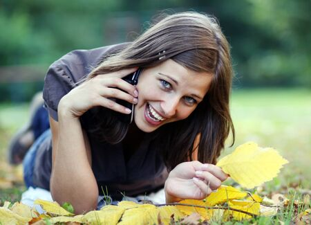 woman calling by phone in autumn park  photo