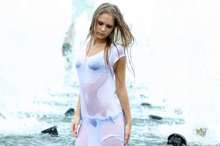 Junge sexy Frau badet in einem Stadtbrunnen