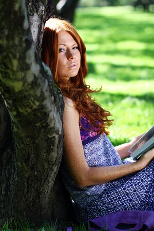 Young woman in summer, green park reading book Stock Photo